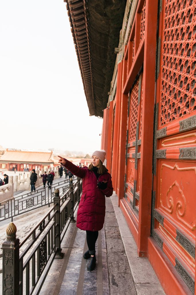 girl pointing at the Forbidden City in Beijing, China