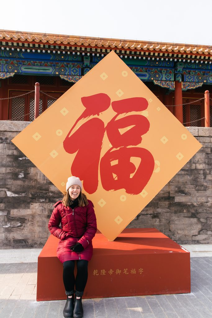 girl sitting in front of Chinese sign