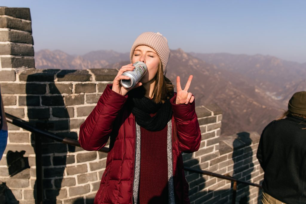 girl drinking beer at the Great Wall of China