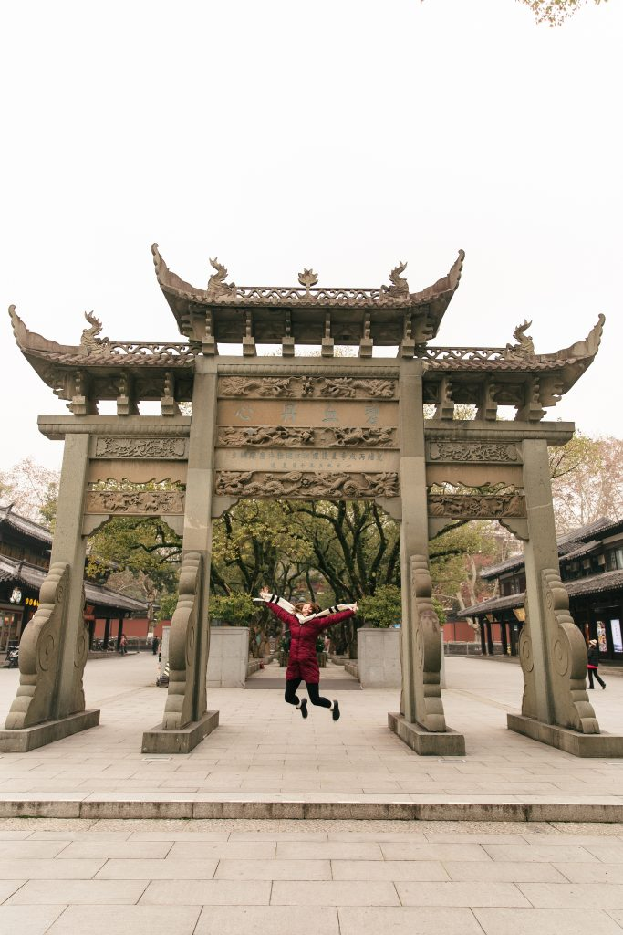 girl jumping in front of Chinese sculpture