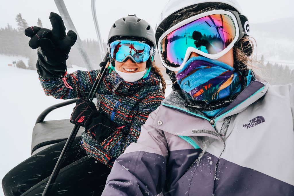 two girls riding ski lift with winter coats and goggles on