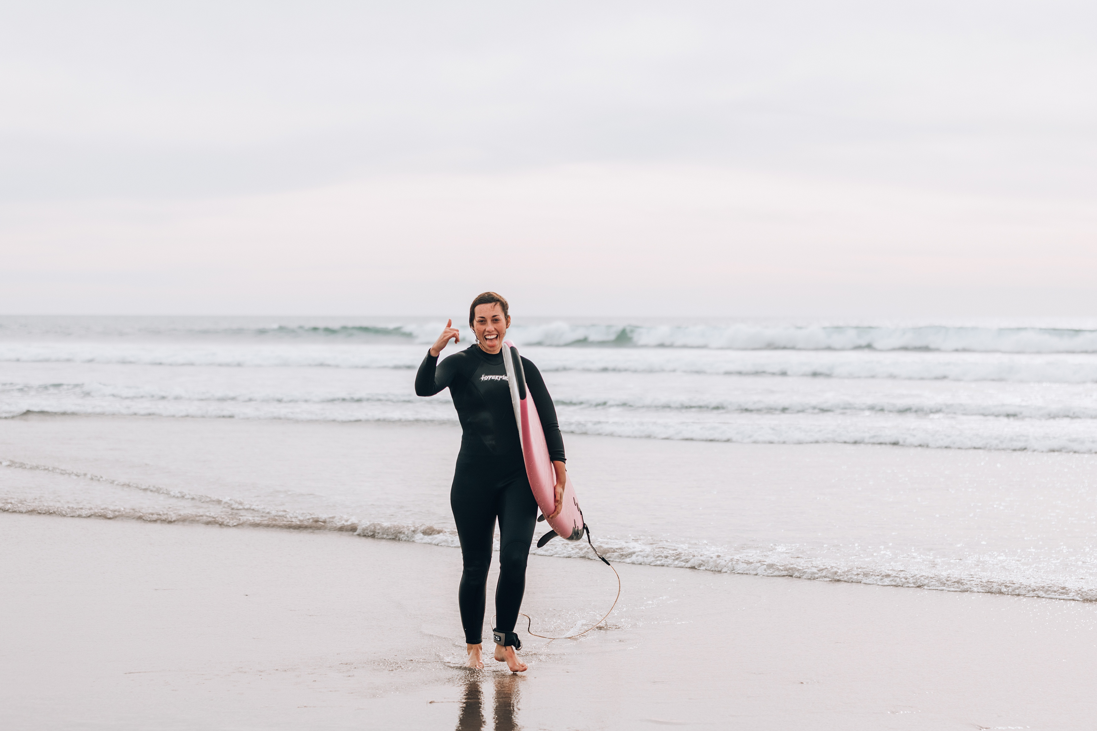 girl walking on beach in wetsuit with surfboard