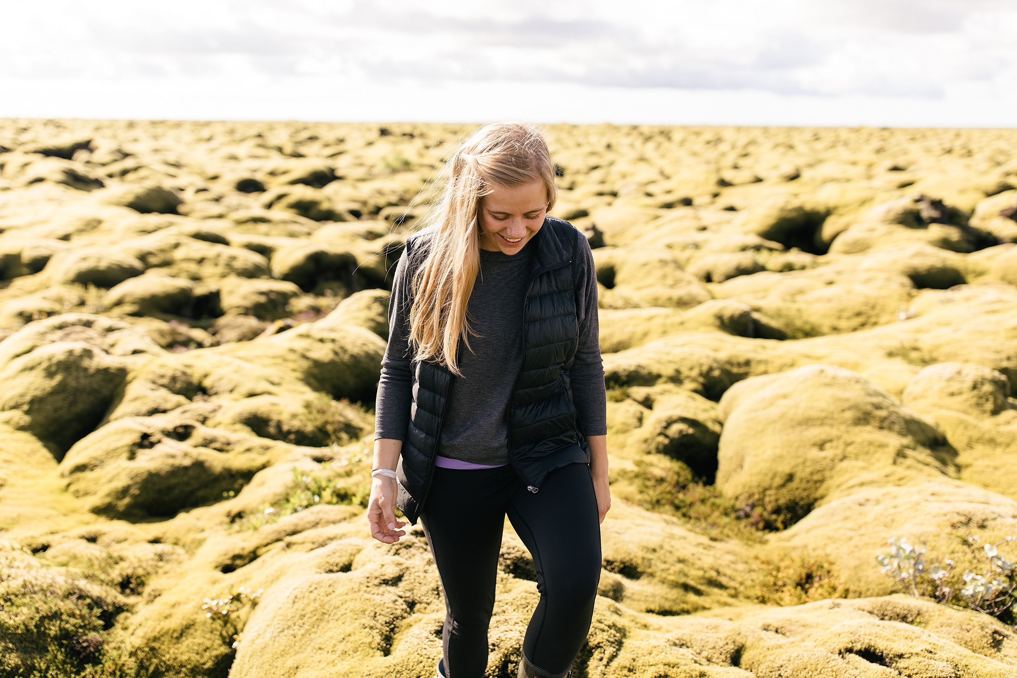 girl walking through Iceland in a black vest